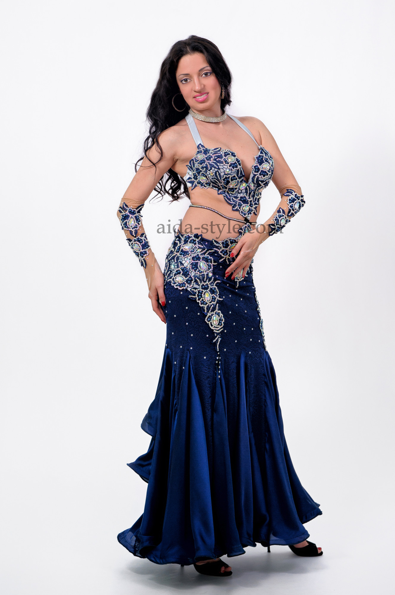 Professional belly dance dress with accessories for both hands. Skirt has flounces. Bra and hips are decorated with stones and flower patterns