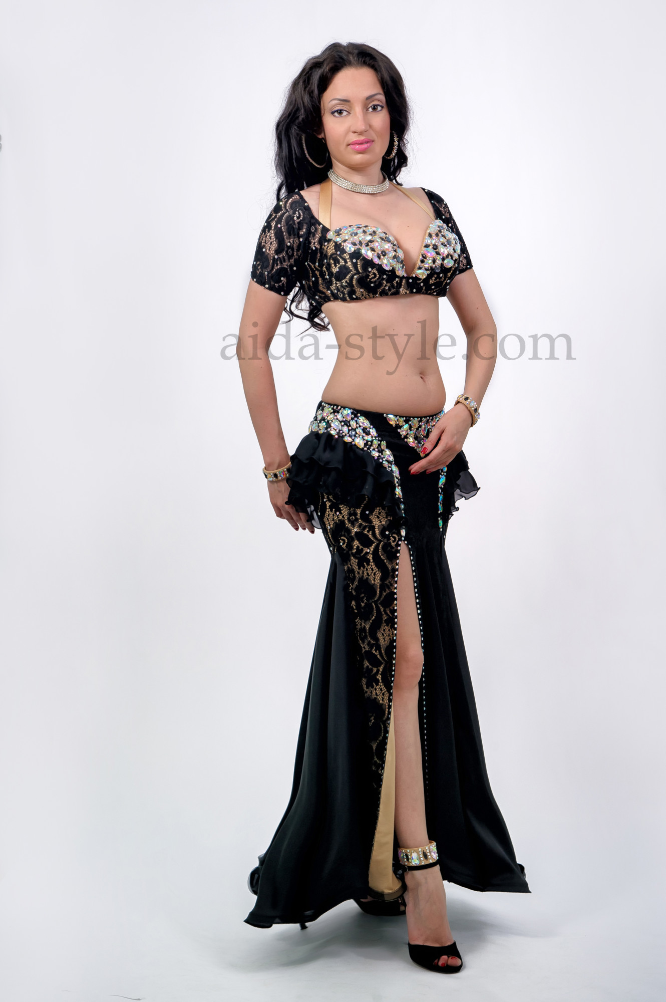 Professional belly dance suit in black and beige color with rich decorations on the bra and hips. The skirt has a cut on the right side