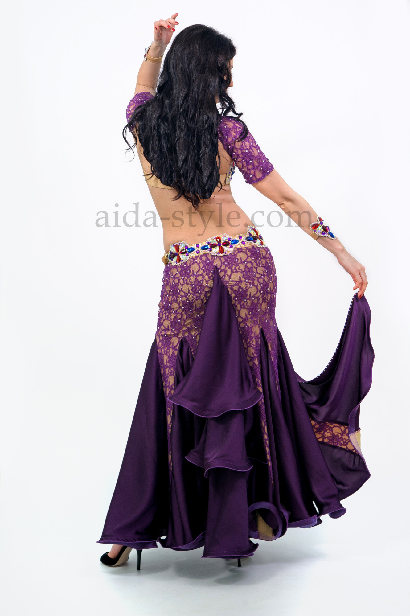 Professional belly dance costume in lilac / violet color. Bra and belt are decorated with big bright stones of red, blue and lilac colors
