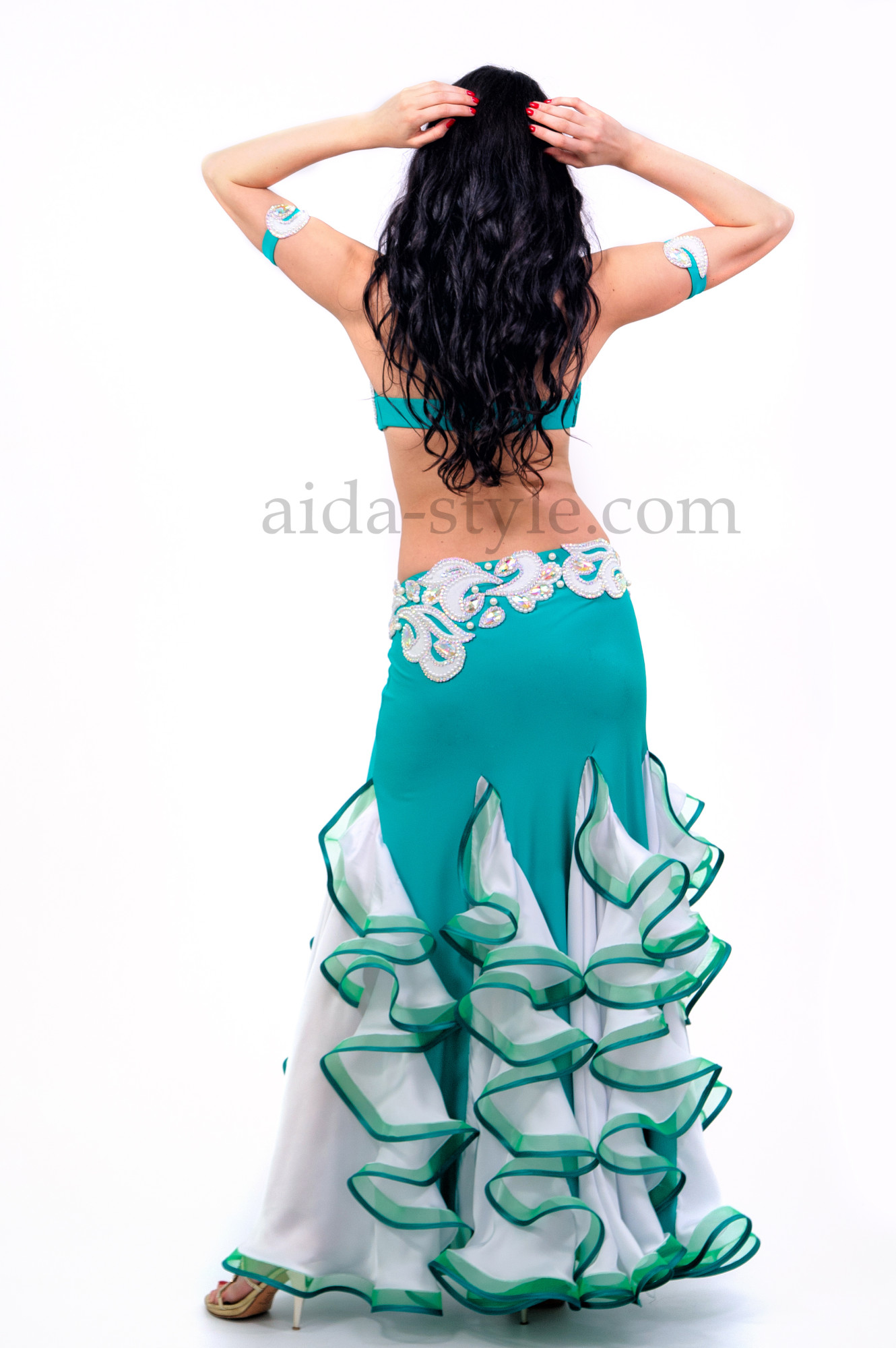 Professional belly dance costume of azure-blue color. Bra and belt are decorated with oriental patterns. The skirt has bouffant ruffles