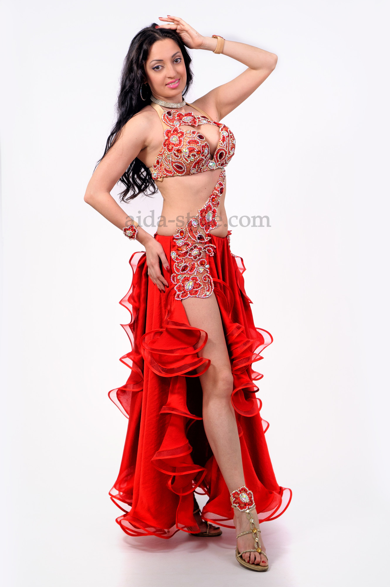 Professional belly dance dress in red color. Bra and right hip are decorated with oriental patterns and stones