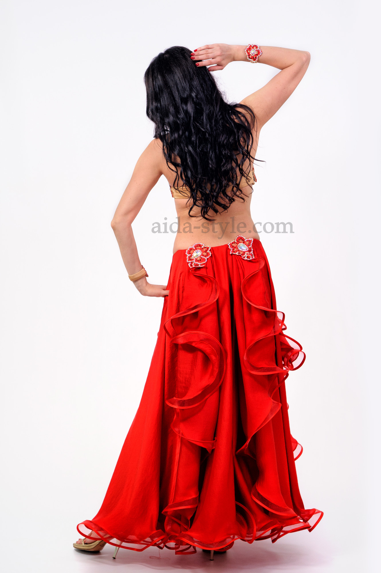 Professional belly dance dress in red color. Skirt has flounces. Bra and right hip are decorated with oriental patterns and stones