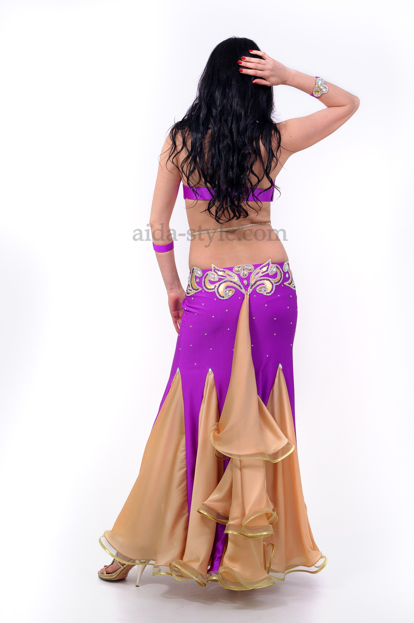 Professional belly dance dress in violet color and with a rich decoration from stones. The flounces are made in beige colour