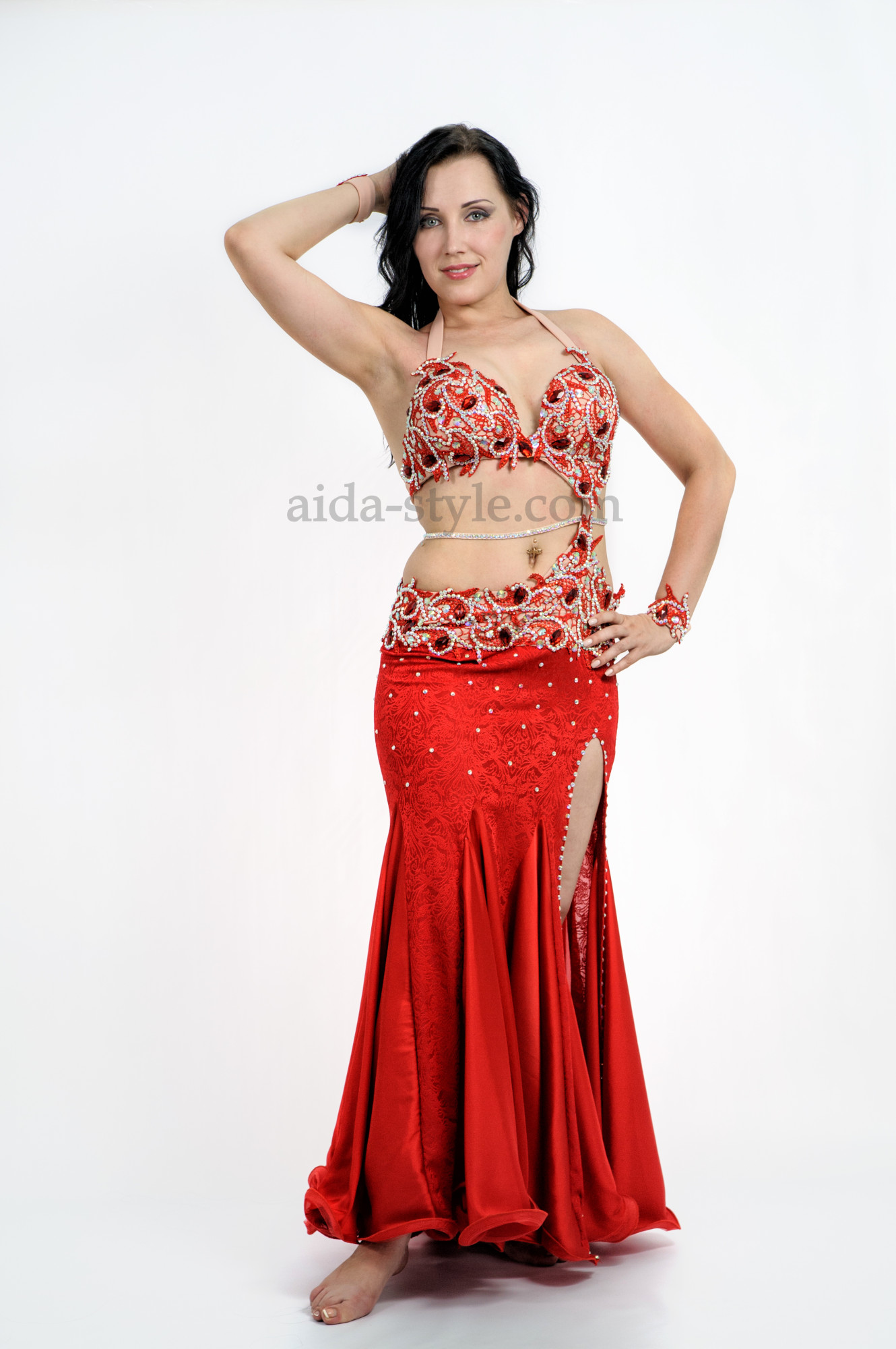 Red professional belly dance dress decorated with stones. The skirt has a cut on the left side. Bra and skirt are connected with a decoration