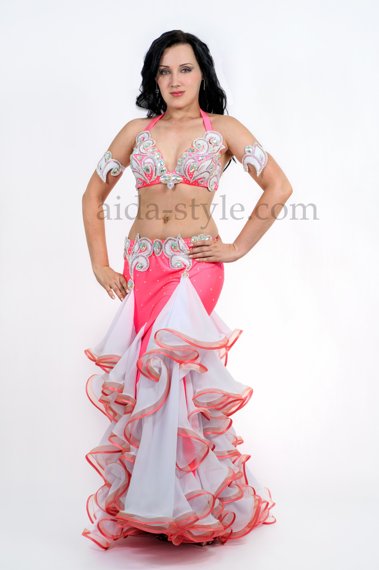 Professional belly dance costume of pink color with white ruffles. The skirt is a mermaid tipe and is skin tight on hips