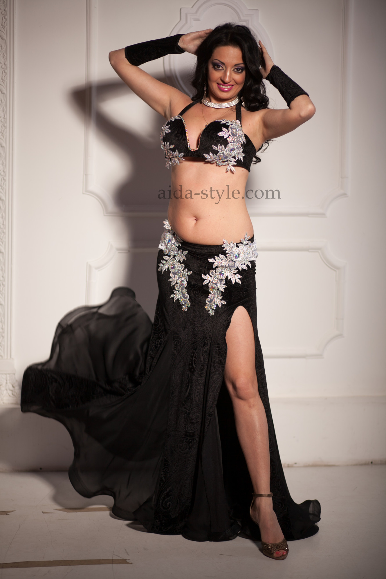 Professional belly dance costume in black color with white applications. The skirt is made from light fabric, with white belt