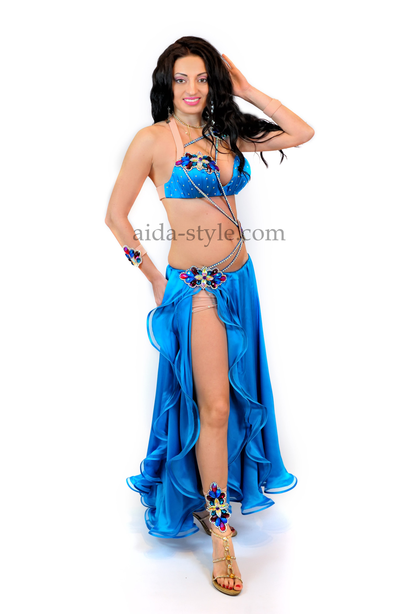 Bright blue professional belly dance costume with flowers from stones on the right hip and on the bra. The skirt has cut on the right side