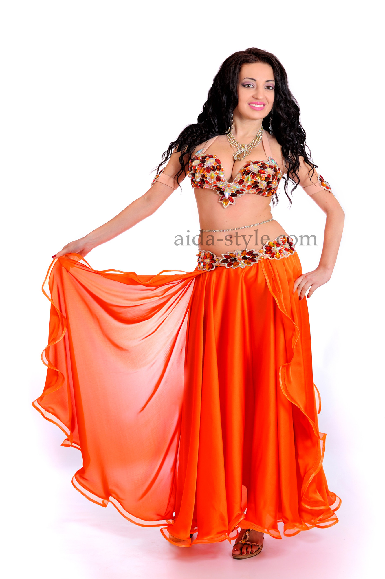 Bright orange professional belly dance suit. Bra and belt are decorated with beautiful brown stones