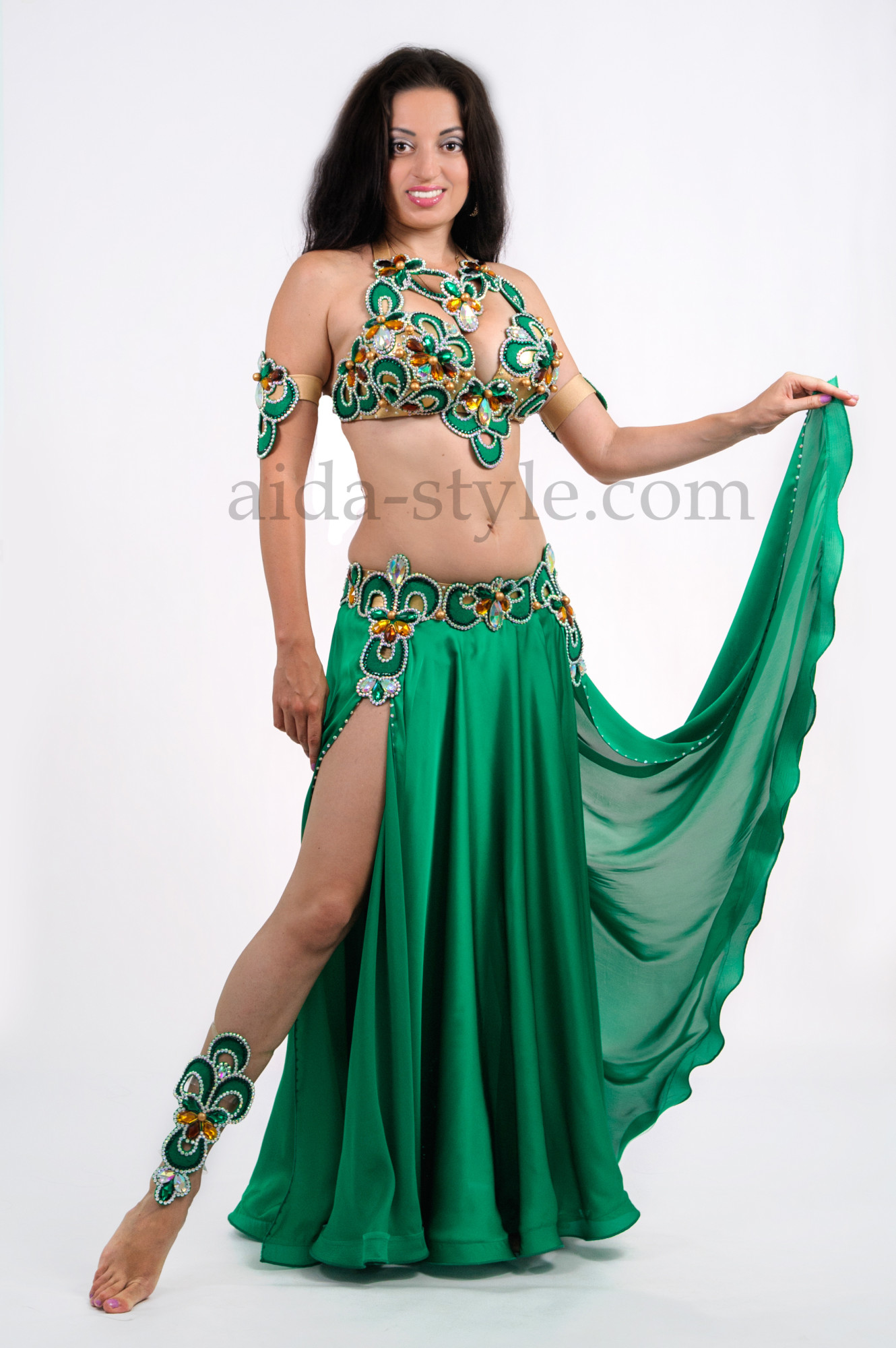 Green professional belly dance costume decorated with bright stones on the bra, belt and around the neck. The skirt has cuts on the roght and left sides