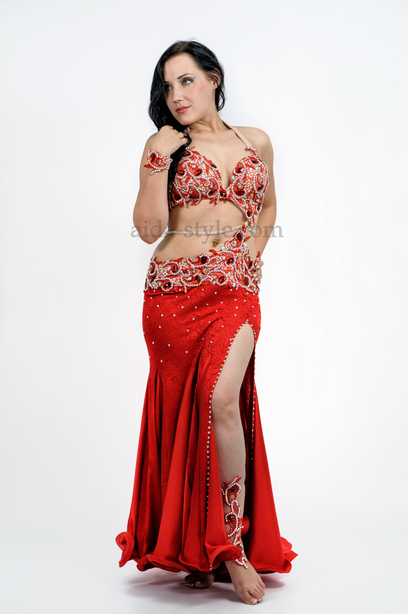 Red professional belly dance dress decorated with stones. The skirt has a cut on the left side