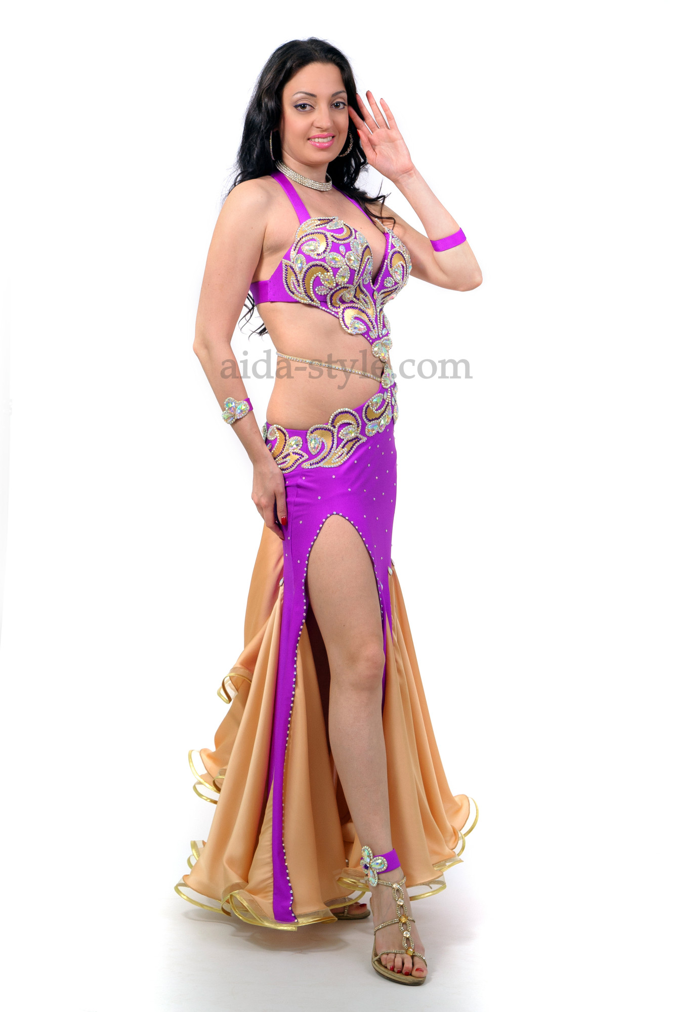 Professional belly dance dress in violet color and with a rich decoration from stones. It has a cut on the right side