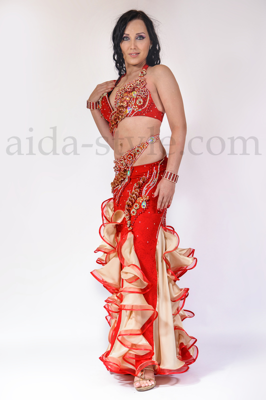 Unique professional belly dance costume in red color with golden flounces, with artificial hand made adornment and big hight quality chrystals. Sits beautiful on the body, is easy to wear and very convenient.
