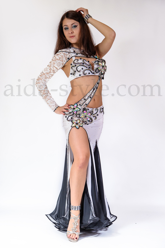 White & black belly dance dress decorated with flower patterns and chrystals. The sleeve is connected to the bra and can not be used separately. The skirt connects to the bra with a closing.