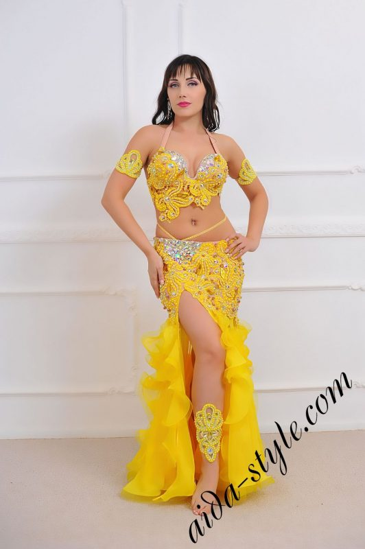 bright yellow oriental outfit for belly dance with rich lace decoration and mermaid skirt